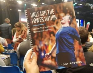 Alice Dartnell Holding  Tony Robbins Event pamphlet Unleash the Power Within