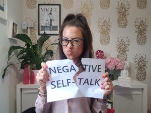 Alice Dartnell Life Success Coach London UK holding up her negative self-talk sign