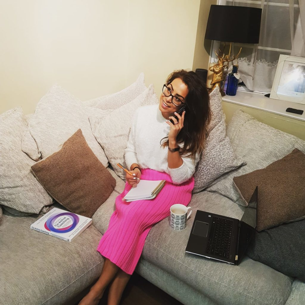 Alice Dartnell Life Success Coach Consultation London sat on sofa working at home writing in note pad
